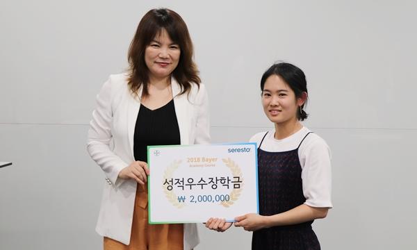 정현진 바이엘코리아 동물의약사업부 대표(왼쪽)가  성적 최우수자 김다미 수의사(오른쪽)에게 장학금을 수여했다